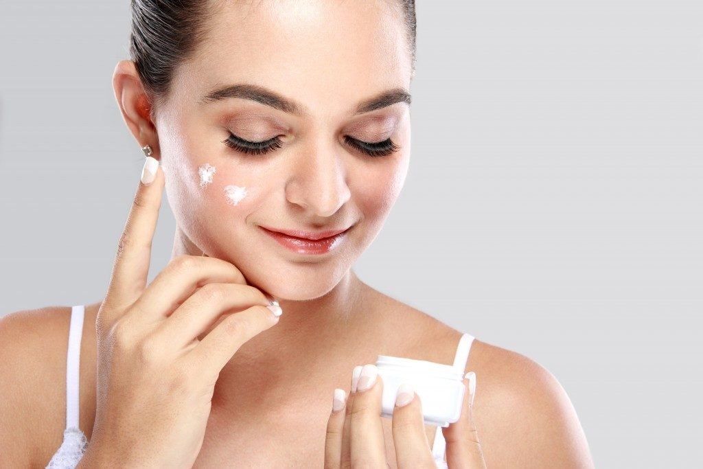 Woman putting moisturizing cream on face