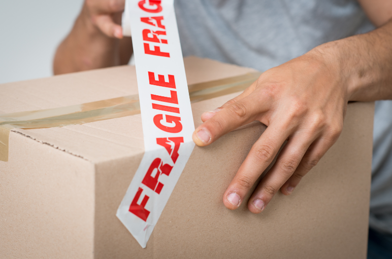 Man putting on fragile tag on the box