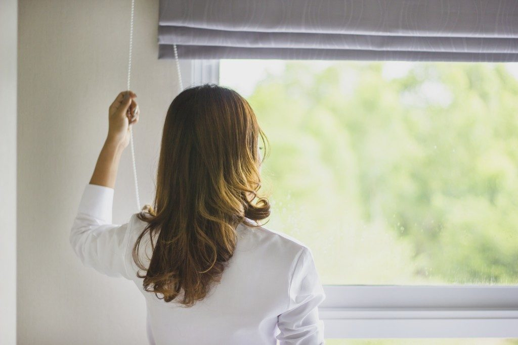 woman looking out of window with downward sliding curtains