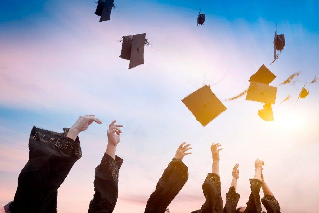 Graduates throwing graduation hats