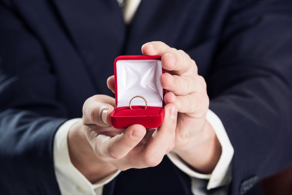 Close up of man holding wedding ring and gift box.
