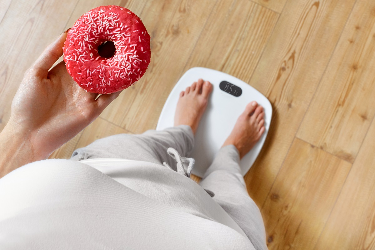 person holding a donut stepping on a scale