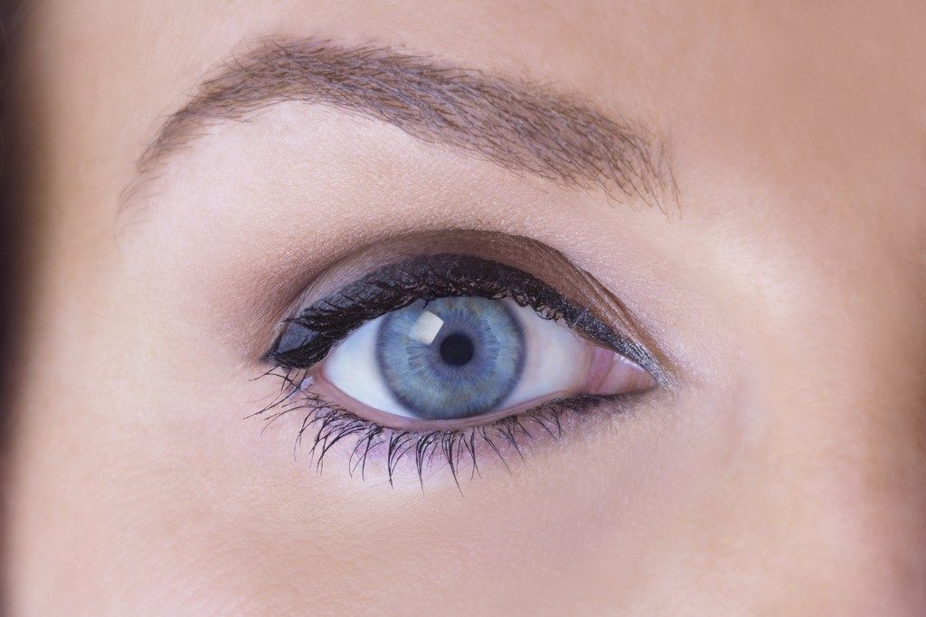 close up of a woman's blue eye and eyebrow