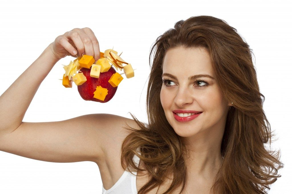 girl holding an apple with cheese cubes