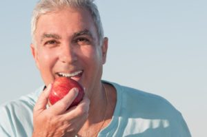 Old man eating an apple
