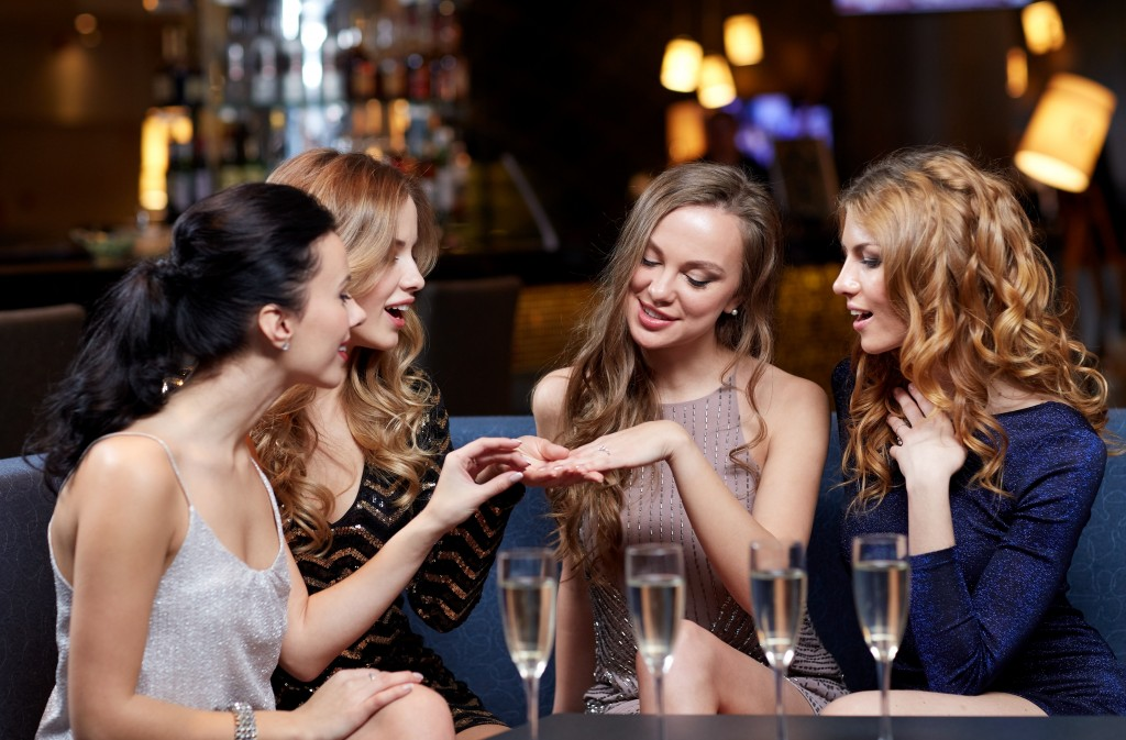 woman showing her engagement ring to her friends