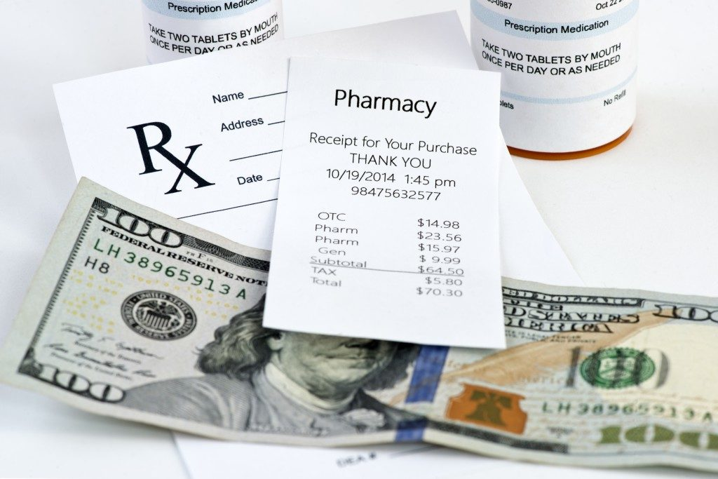 Pharmacy receipt with prescription bottle and prescription on neutral background