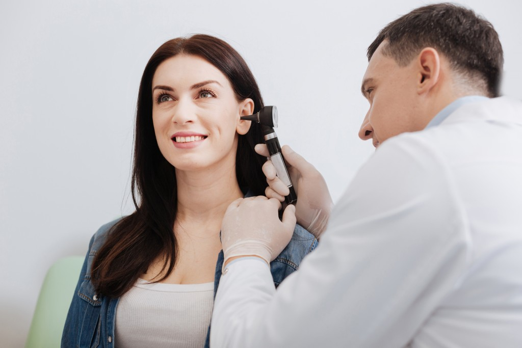 ENT doctor checking woman's ear