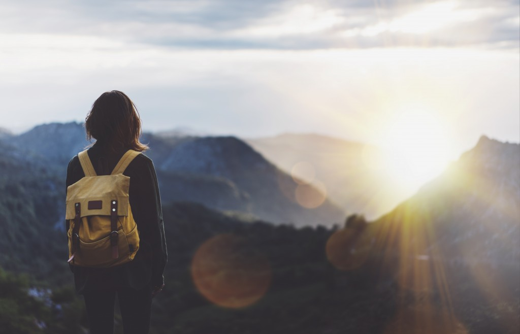 young girl with backpack enjoying sunset on peak of foggy mountain