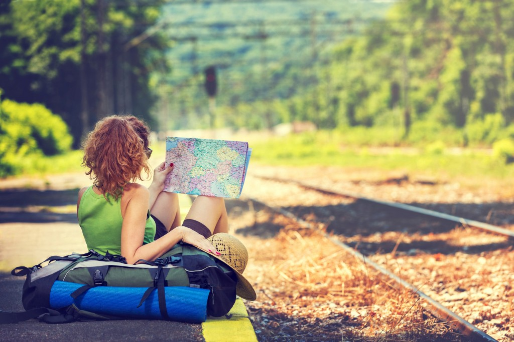 Girl wearing backpack holding map, waiting for a train.