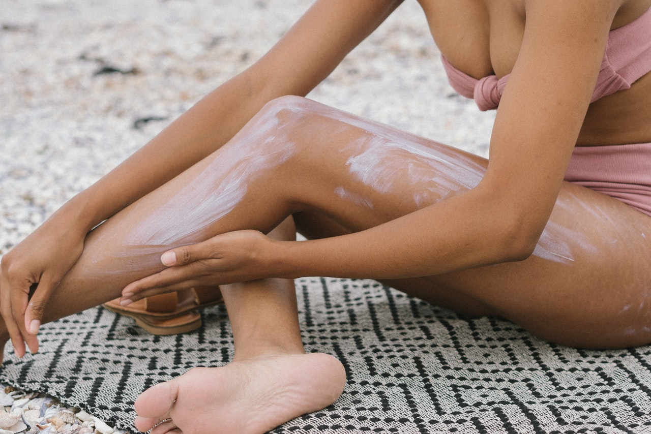 woman applying lotion to her legs
